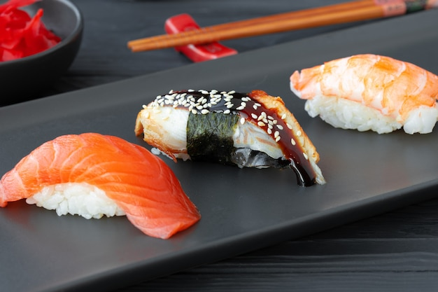 Nigirisushi met zalmpaling en garnalen die op zwarte ceramische plaat worden gediend