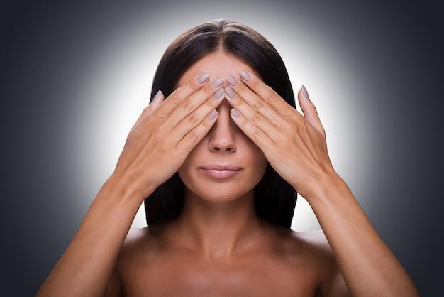 Niks zien! portret van een jonge shirtloze vrouw die de ogen bedekt met de handen terwijl ze tegen een grijze achtergrond staat