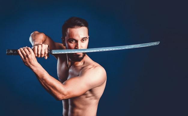 Ninja samoeraienstrijder met naakte torso in aanvalshouding met katana-zwaard