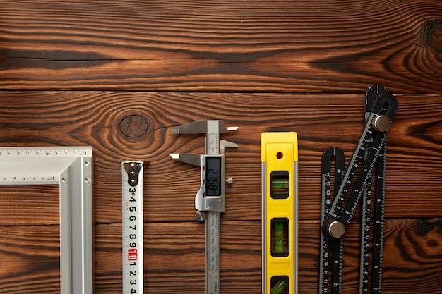 Niveau en hoek, liniaal en remklauw, houten tafel, bovenaanzicht. professioneel meetinstrument, timmermansuitrusting, timmermansgereedschap