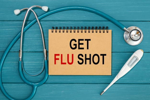 Nmedical concept - stethoscoop met notitieboekje en klembord schrijven get flu shot