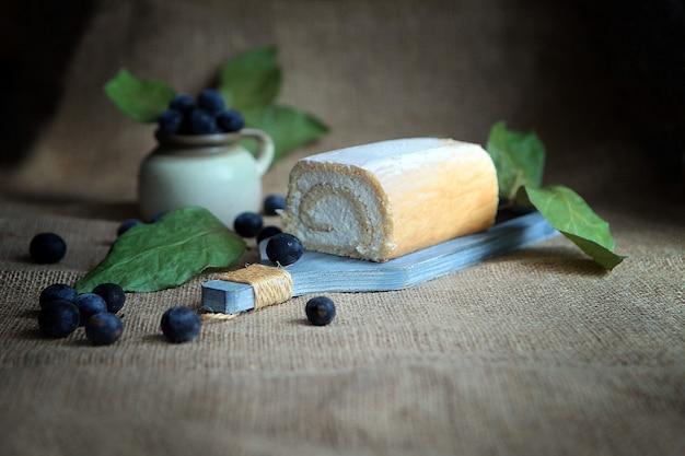 No bake curd roll cake gevuld met kokosroom en pruimen, rustieke stijl.