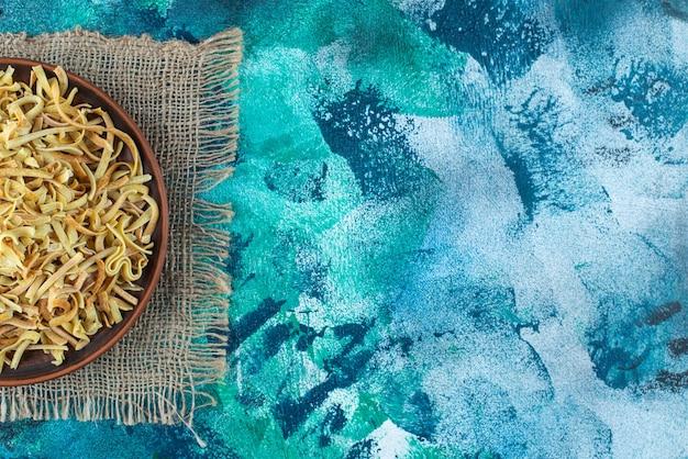 Noedel in een kom op een textuur, op de blauwe achtergrond.
