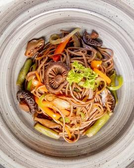Noedels bereid met champignons, paprika en saus