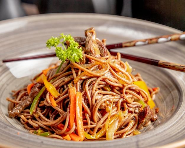 Noedels bereid met paprika en saus van vlees