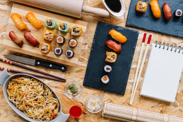 Noedels dichtbij sushi en notitieboekje