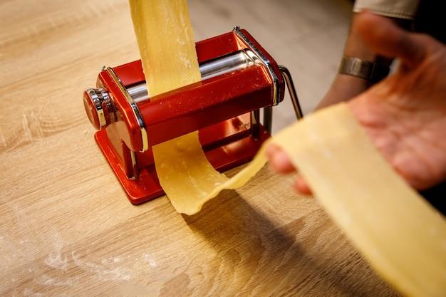 Noedels en pastamachine en lang stuk deeg in handen.