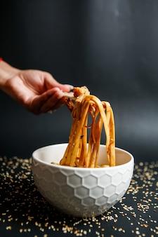 Noedels gemengd met champignons en gegarneerd met sesamzaadjes