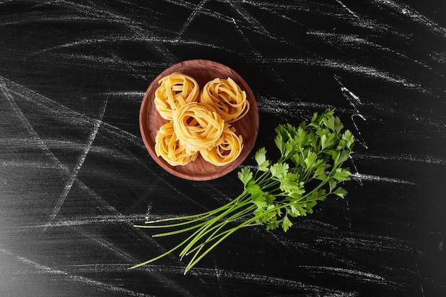 Noedels geserveerd met een bosje verse peterselie.