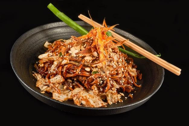 Noedels in een zwarte kom met cashewkool, gebakken uien, sesam en wortelen met stokjes bovenaanzicht