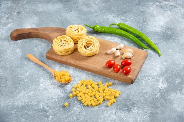 Noedels, knoflook en tomaten op een houten bord.