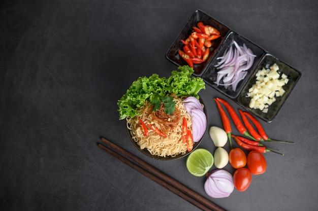 Noedels kruidig in de kom met ingrediënten en eetstokjes op zwarte cementoppervlakte, hoogste mening