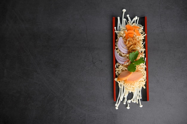 Noedels kruidig in houten dienblad met ingrediënten op zwarte cementoppervlakte.