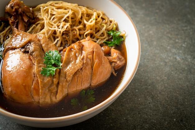 Noedels met gestoofde kip in bruine soepkom - asian food style