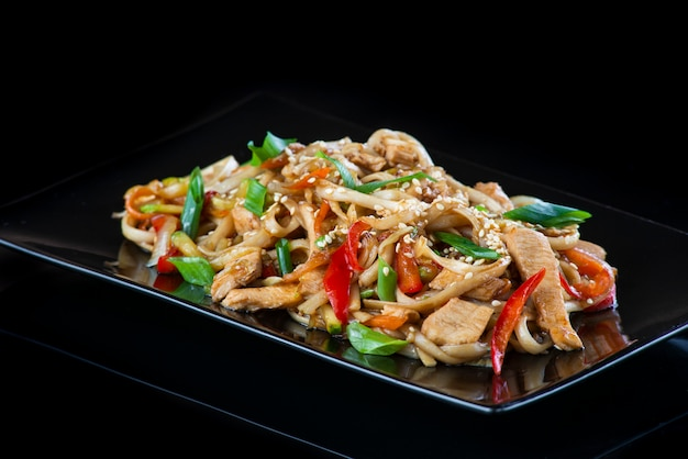 Noedels met groenten met varkensvlees, kip, vis, sint-jakobsschelp, rundvlees, garnalen in een zwarte plaat op een zwarte muur.
