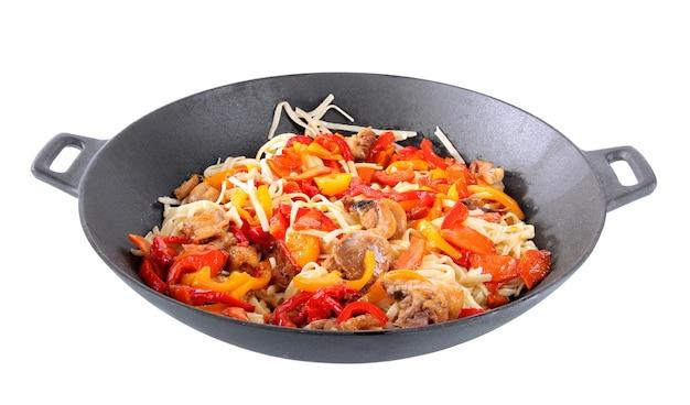 Noedels met groenten op wok die op wit wordt geïsoleerd