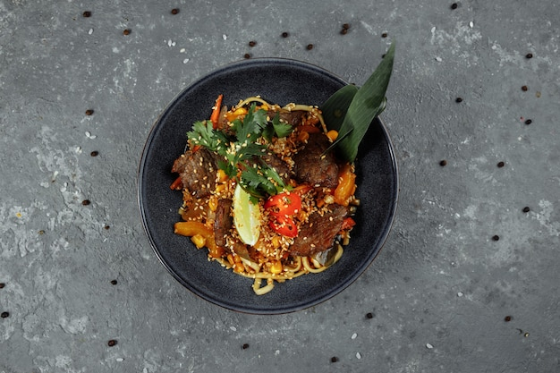 Noedels met kalfsvlees en groenten op een grijze tafel