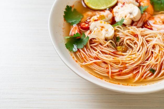 Noedels met pittige soep en garnalen in witte kom (tom yum kung) - aziatische eetstijl