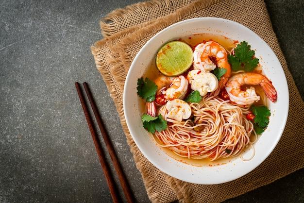 Noedels met pittige soep en garnalen in witte kom (tom yum kung). aziatische eetstijl