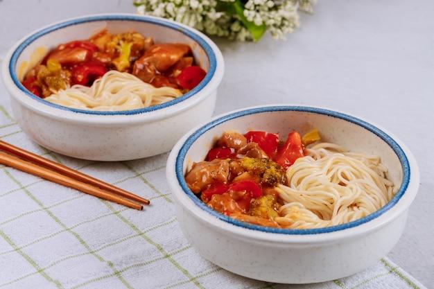 Noedels met roergebakken kip en groenten in kommen en eetstokjes. bovenaanzicht. aziatische keuken.