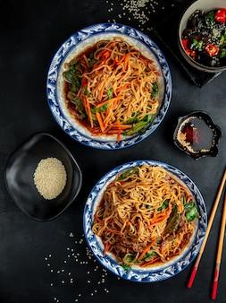 Noedels met rundvlees en groenten op zwarte tafel