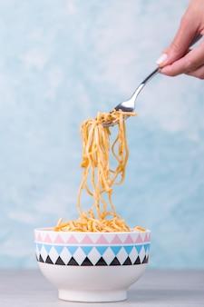 Noedels met saus in een gekleurde kom, hand houdt een vork van pasta opknoping, eetlust spaghetti op blauw.