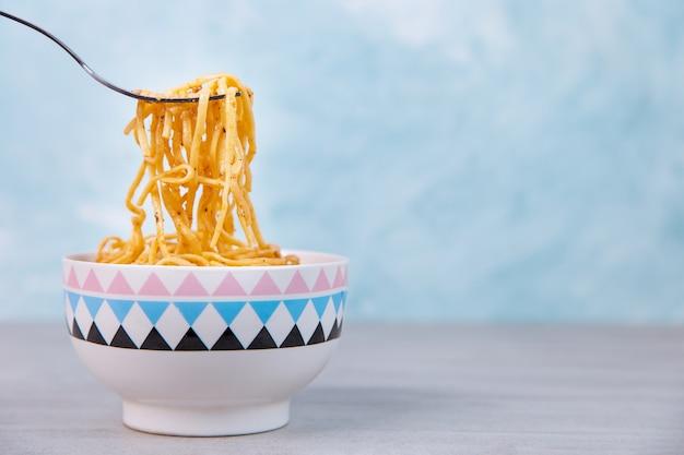 Noedels met saus in een gekleurde kom met vork, eetlustspaghetti op blauw.