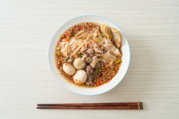 Noedels met varkensvlees en gehaktballen in pittige soep of tom yum noedels in aziatische stijl