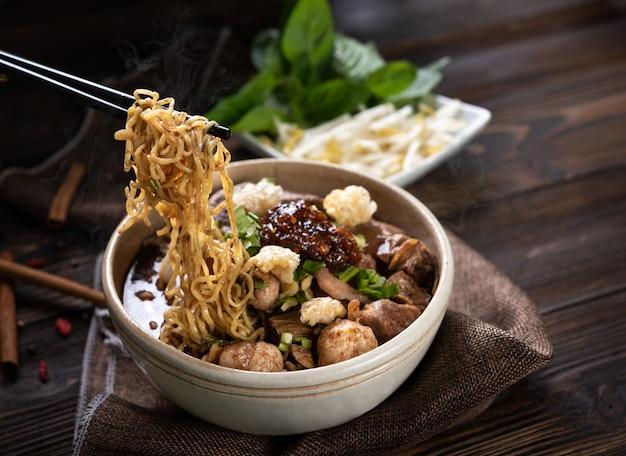 Noedels met varkensvlees en varkensballetjes, chilipasta met soep op thaise wijze en groente. boot noedels. selectieve focus