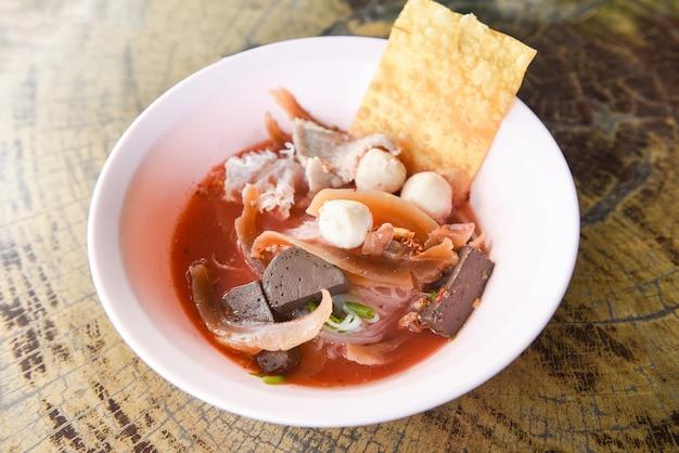 Noedels met zeevruchten op rode soep - hete en kruidige thaise de bal van de het varkensvleesvissen van de noedelinktvis