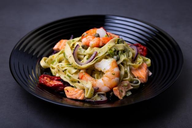 Noedels met zeevruchten, zongedroogde tomaten, kappertjes en rode uien. huisgemaakte pasta met garnalen, zalm (forel) en pestosaus. zwarte achtergrond, zwarte plaat. detailopname.
