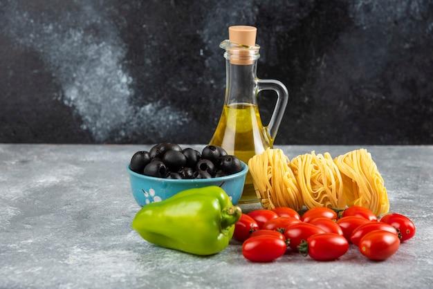 Noedels, olie en diverse groenten op stenen tafel.