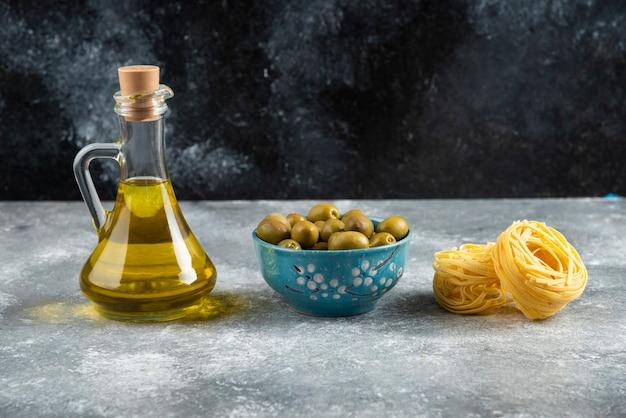Noedels, olie en groene olijven op stenen tafel.