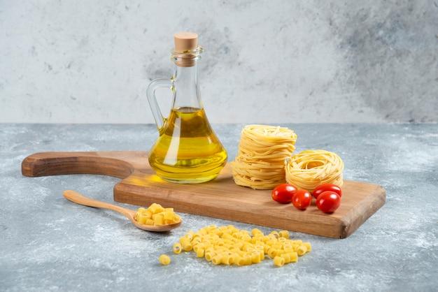 Noedels, olijfolie en tomaten op een houten bord.