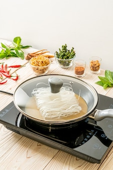 Noedels op pan zetten met saus klaar om te roerbakken
