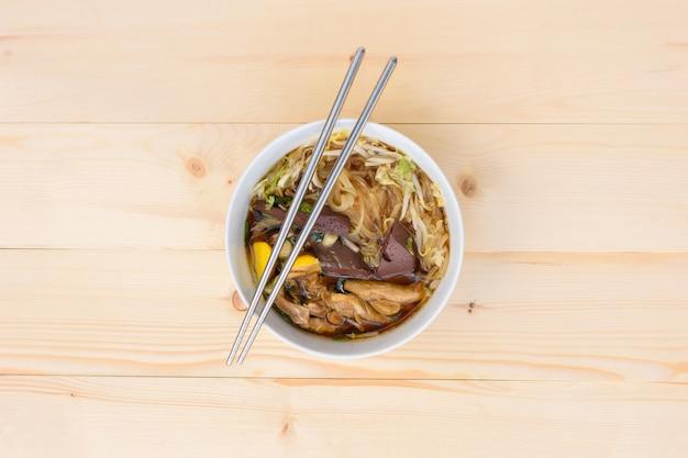 Noedelsoep met stokjes in kom op een houten tafel, bovenaanzicht, thais lokaal eten
