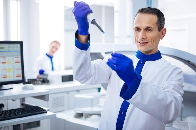 Nog een druppel. bekwame aantrekkelijke mannelijke gekke werker die medicatie laat vallen met een pipet in een flesje dat hij in zijn hand houdt terwijl hij naast de computer staat