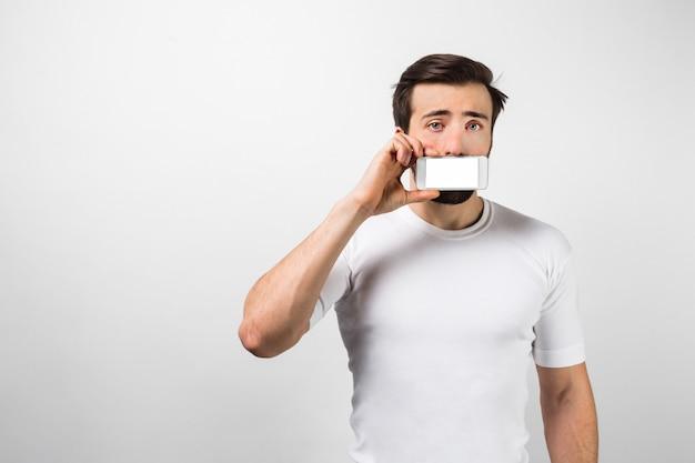 Nog een foto van de donkerharige man die in de buurt van de witte muur staat en een helder scherm van de telefoon naar de camera toont. hij ziet er tegelijkertijd doodsbang en verdrietig uit. geïsoleerd op witte muur.