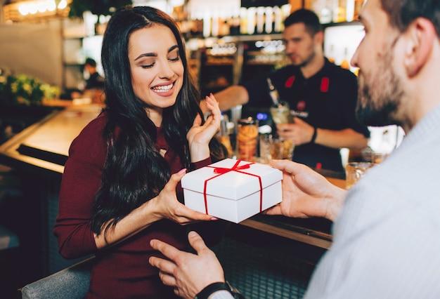 Nog een foto van de man die een geschenk geeft aan zijn geliefde meisje. ze accepteert het met een glimlach en plezier. ze kijkt naar het heden.