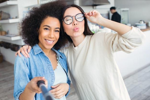 Nog een foto van twee vrienden. ze maken selfie. het meisje in blauw overhemd houdt een selfiestok en glimlacht terwijl haar vrienden stelt en kusjes verzendt