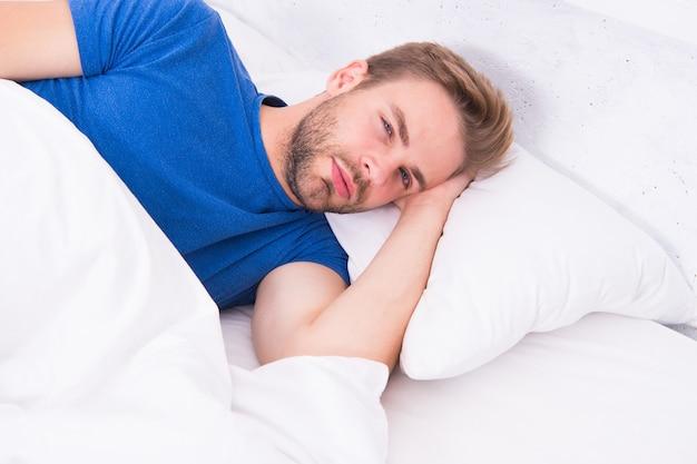 Nog een minuutje in bed. slaperige man liggend in bed bij het ontwaken in de ochtend. vermoeide man die in bed valt. zijn bed voor mij.