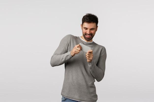 Nog een niveau. vrolijke knappe bebaarde volwassen man in grijze trui, smartphone horizontaal vasthouden en buigen om racecirkel te passeren, applicatie spelen, mobiel spel, vreugdevol glimlachen