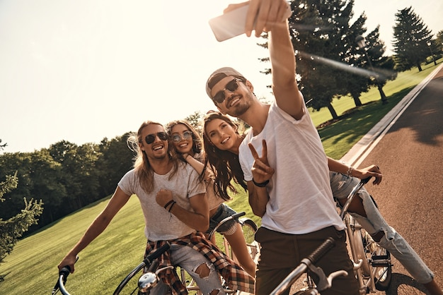 Nog maar een schot. groep gelukkige jonge mensen in vrijetijdskleding die selfie nemen en glimlachen terwijl ze samen buiten fietsen
