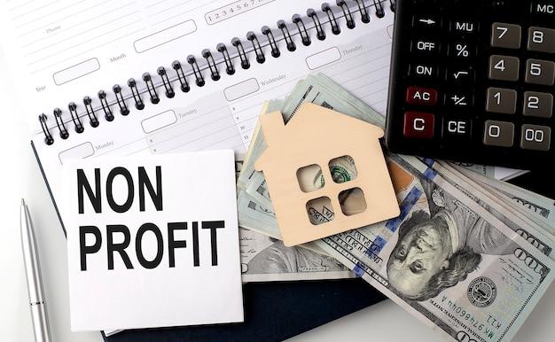 Non profit - de inscriptie van tekst op de sticker over planning met dollars en rekenmachine