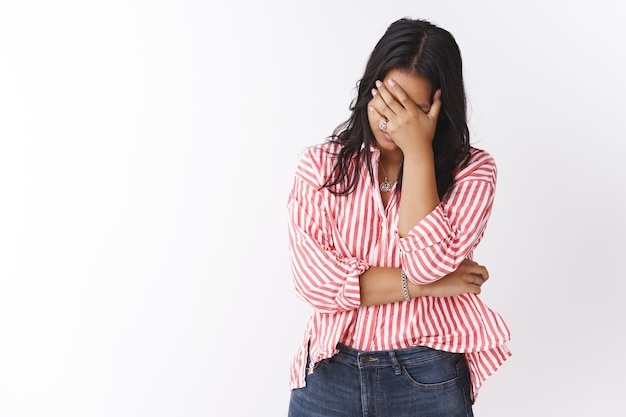 Nood, druk en depressie concept. portret van een vermoeide en uitgeputte vrouw die zich zorgen en perplex voelt, niet wetende wat een moeilijke periode moet zijn, waardoor het gebaar van de gezichtspalm uitgeput raakt