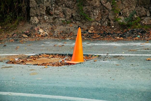 Noodhekwerk met oranje kegel op de weg