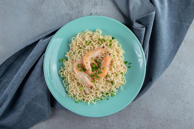 Noodle en garnalen op een bord op een stuk stof, op het marmeren oppervlak.