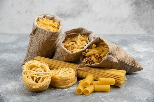 Noodle- en pastasoorten in rustieke manden en marmeren tafel.