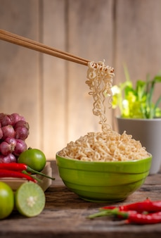 Noodle in een bowlwith limoen en chili en ui en groente op houten tafel