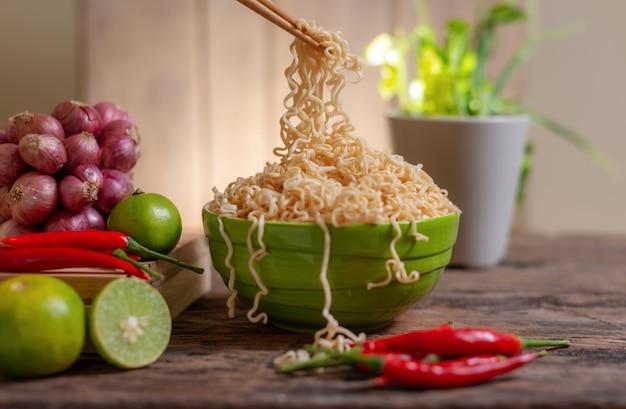 Noodle in een kom met limoen en chili en ui en groente